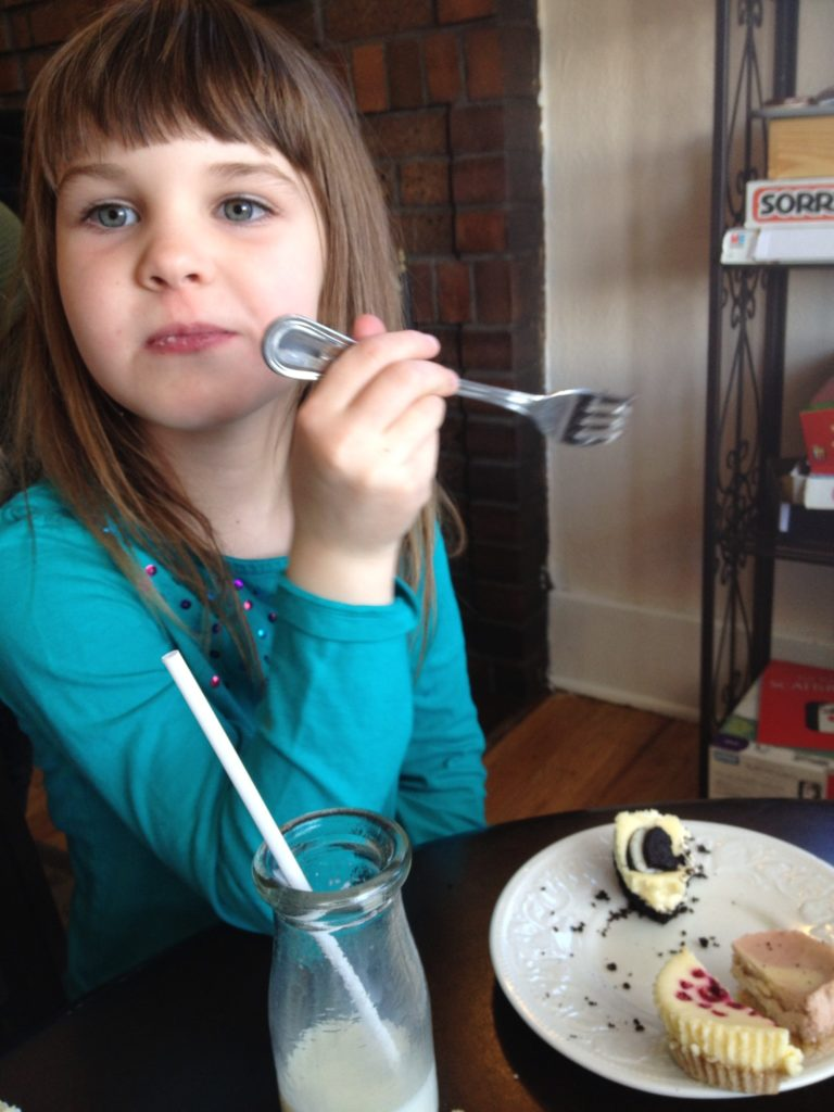 Izzy elegantly eating some gourmet cheesecake.